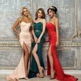 Drie dames in avondjurken stock afbeelding