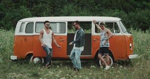 Drie dansers hebben samen een grote tijd bij de picknick, bewegen zich zeer charismatisch voor een retro bestelwagen stock videobeelden