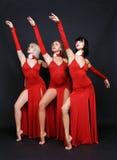 Drie dansers in rode avond kleden Royalty-vrije Stock Foto's