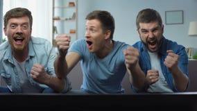 Drie de beste vrienden het letten op sportconcurrentie op TV die thuis, van goed spel genieten stock footage