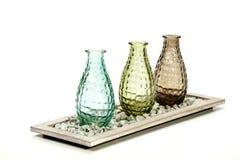 Drie Decoratieve Glasvazen op Tribune met Kiezelstenen Stock Foto