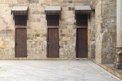 Drie deuren in een steenmuur bij de belangrijkste binnenplaats in historisch stock fotografie