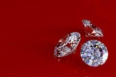 Drie diamanten op rode glanzende achtergrond Royalty-vrije Stock Fotografie