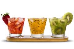 Drie die dranken met passievrucht, aardbei en kiwi Caipir worden gemaakt Royalty-vrije Stock Foto's