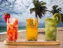 Drie die dranken met passievrucht, aardbei en kiwi Caipir worden gemaakt Royalty-vrije Stock Fotografie
