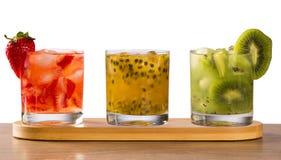 Drie die dranken met passievrucht, aardbei en kiwi Caipir worden gemaakt Stock Afbeeldingen