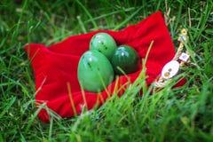 Drie die eieren van steenjade worden gemaakt liggen op rode zak Royalty-vrije Stock Afbeelding