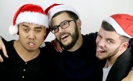Drie die mensen bij Kerstmis worden gedronken Stock Fotografie