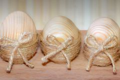Drie die paaseieren in streng in de vorm van een nest op een houten achtergrond worden verpakt stock fotografie