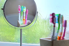 Drie die tandenborstels in een spiegel worden weerspiegeld Stock Afbeelding