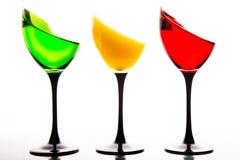 Drie die wijnglazen met de kleuren van verkeerslichten worden gevuld stock afbeelding
