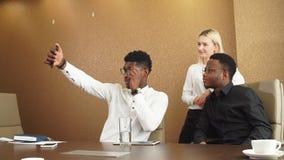 Drie diverse prettige medewerkers die zelfportret nemen op kantoor stock video