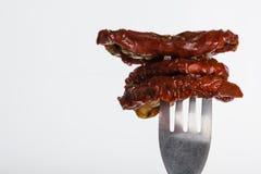 Drie droge die tomaten op vork worden gespietst Stock Fotografie