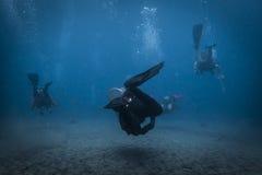 Drie duikers die vanaf de camera zwemmen stock afbeeldingen