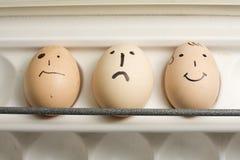 Drie eieren die met menselijke gezichten worden geschilderd stock fotografie