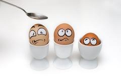 Drie eieren met bang gemaakt gezicht in eierdopje Royalty-vrije Stock Afbeeldingen
