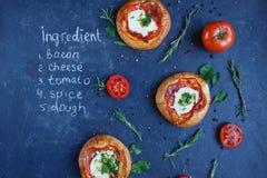 Drie Eigengemaakt Mini Pizza met Tomaten, Kaas en Bacon, Verwondingen en Kruiden op een donkere achtergrond met een geschreven re stock foto