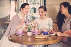 Drie elegante jonge dames in een koffie stock afbeeldingen