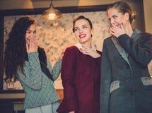 Drie elegante jonge dames klaar voor een partij stock afbeelding