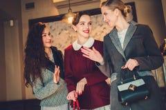 Drie elegante jonge dames klaar voor een partij stock foto