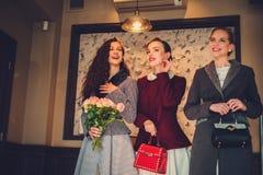 Drie elegante jonge dames klaar voor een partij royalty-vrije stock foto