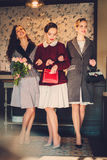 Drie elegante jonge dames klaar voor een partij stock afbeeldingen