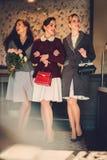 Drie elegante jonge dames klaar voor een partij royalty-vrije stock afbeelding