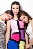 Drie elegante mooie die meisjes op witte achtergrond worden geïsoleerd Stock Afbeeldingen