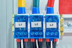 Drie elektrokabels of draden worden verbonden met de distributieeenheden stock foto's