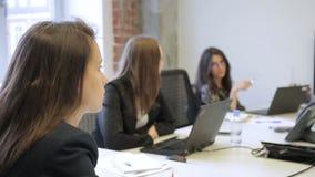 Drie en vrouwen die terwijl het zitten bij lijst met laptops in bureau luisteren spreken stock videobeelden