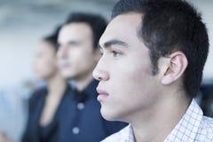 Drie ernstige bedrijfsmensen die in een commerciële vergadering zitten stock fotografie