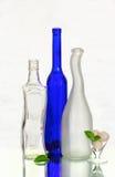 Drie flessen en een wijnglas met snoepjes Royalty-vrije Stock Fotografie