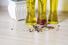 Drie flessen olijfolie met kruiden Stock Afbeelding