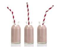 Drie Flessen roze melk met rood en wit gestreept stro royalty-vrije stock fotografie
