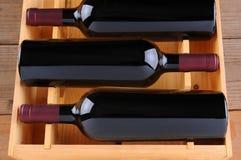 Drie Flessen van de Rode Wijn in Houten Geval stock foto's