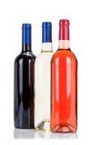 Drie flessen wijn die op wit wordt geïsoleerda Stock Foto