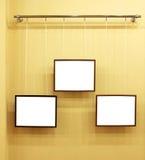 Drie frames met canvas op de tentoonstellingsrichel Royalty-vrije Stock Foto