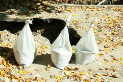 Drie gaat het witte plastic zakkenhoogtepunt van zand voor de geul op de plaats van de straatwederopbouw en met de oranje herfst  Stock Foto's