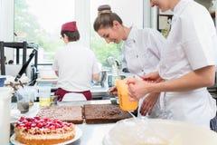Drie gebakjebakkers die in banketbakkerij vlaaien voorbereiden stock foto's