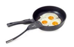 Drie gebraden eieren in de pan en de spatel Stock Afbeeldingen