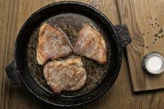 Drie gebraden varkensvleeslapjes vlees in een pan Stock Fotografie
