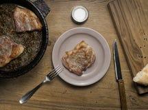 Drie gebraden varkensvleeslapjes vlees in een pan Royalty-vrije Stock Foto
