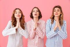 Drie geconcentreerde jonge meisjesjaren '20 die kleurrijke gestreepte paja dragen Stock Afbeeldingen