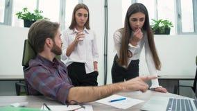 Drie geconcentreerde teamleden bespreken het project en onderzoeken de computer, die de beste oplossing proberen te vinden stock video