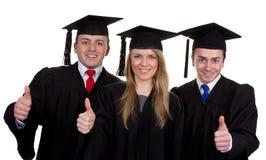 Drie gediplomeerden met duimen ondertekenen omhoog, geïsoleerd op wit royalty-vrije stock foto