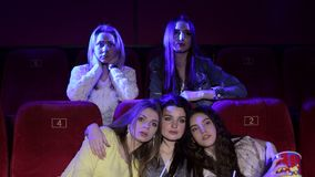 Drie gefrustreerde jonge meisjes die op een uninteresting film letten bij de bioskoop stock footage