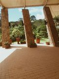 Drie gehelde rotskolommen met bruin bricked vloer en groen gebladerte op de achtergrond in Caleruega, Batangas, Filippijnen stock afbeeldingen
