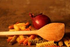 Drie-gekleurde deegwaren met het koken van lepel op steenachtergrond Stock Foto