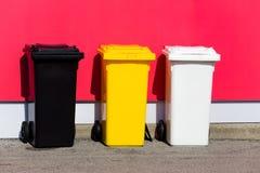 Drie gekleurde kringloopbakken op de straat stock fotografie