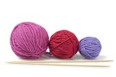 Drie gekleurde wolballen en naalden Stock Afbeelding